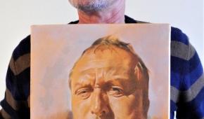 Artysta z jednym ze swoich autoportretów.  Fot.P.Reising